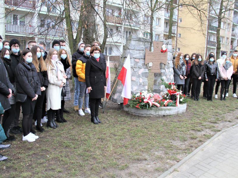Na zdjęciu uczniowie szkół ponadpodstawowych przy pomniku Żołnierzy Wyklętych. Wszyscy w maseczkach