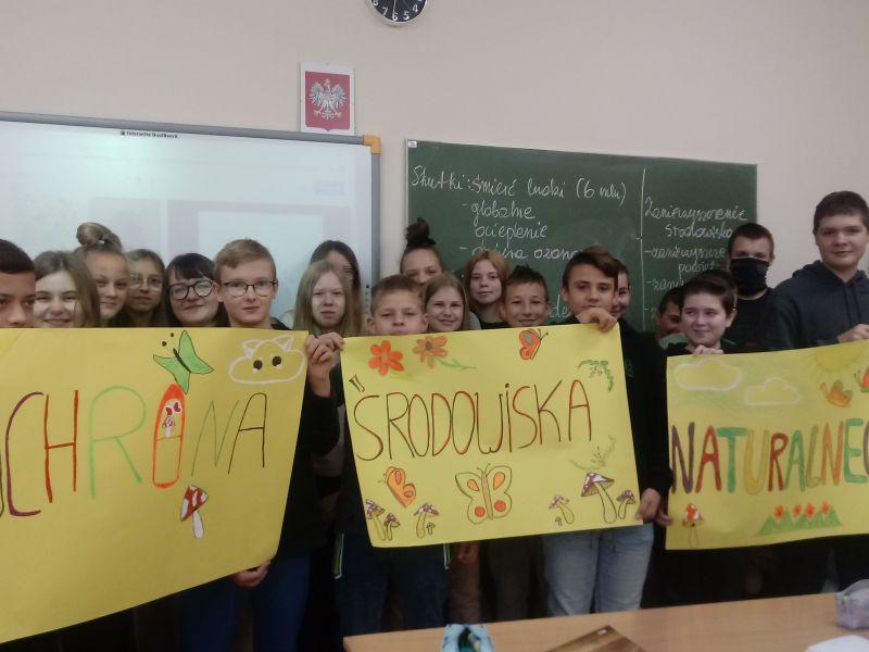 Na zdjęciu stoi grupa młodziezy szkolnej z własnoręcznie wykonanymi plakatami na temat ochrony środowiska. Zdjęcie wykonano w pracowni szkolnej, w tle tablica oraz slip-chart