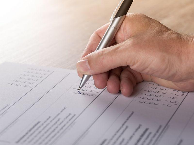 Na zdjęciu widoczna ręka trzymająca długopis podczas wypełniania ankiety