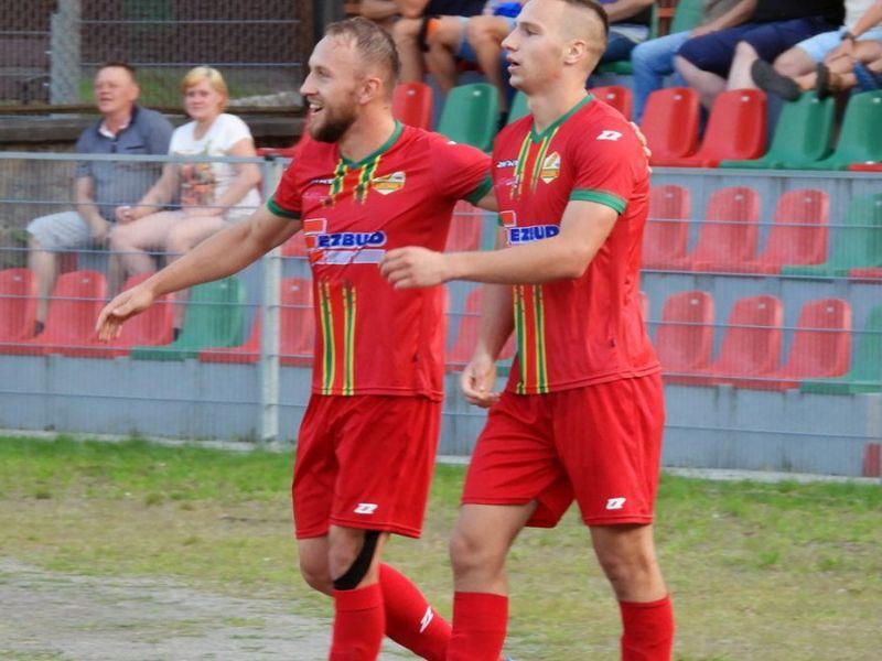 Na zdjęciu dwaj piłkarze Lechii na boisku podczas meczu w czerwonych koszulkach klubowych