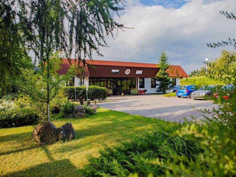 Na zdjęciu wiodoczny jest budynek ORDN. Widok między drzewami. Przed parking z samochodami